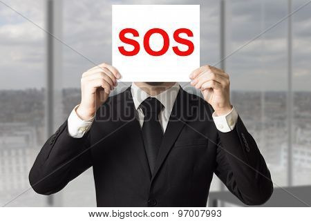 Businessman Hiding Face Behind Sign Sos
