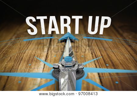 The word start up and compass against wooden table
