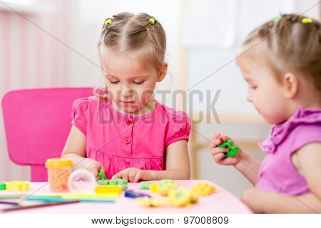Little girls creating from play dough