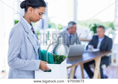 Businesswoman holding box with her colleagues behind her in office