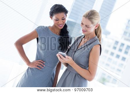 Businesswoman showing her phone to her colleague in the office