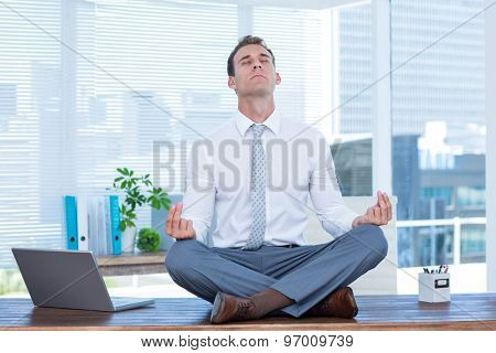 Zen businessman doing yoga meditation on the desk