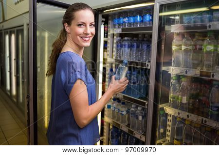 Pretty woman taking bottle of water in fridge at supermarket