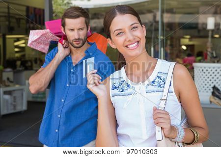 Young happy woman with a concerned man holding shopping bags behind her while shopping