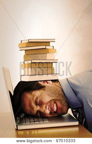 Businessman resting head on keyboard against grey room