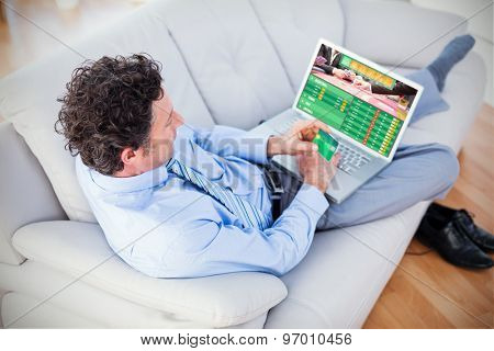 Businessman doing online shopping on couch against gambling app screen