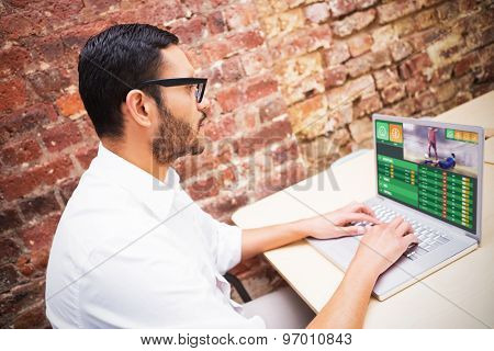 Gambling app screen against concentrated businessman using laptop at desk