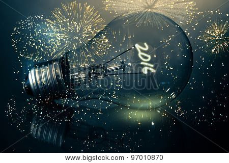 Colourful fireworks exploding on black background against 2016 light bulb