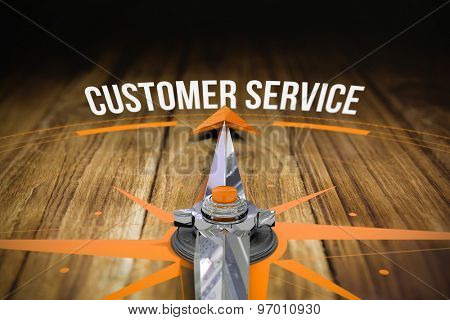 The word customer service and compass against wooden table