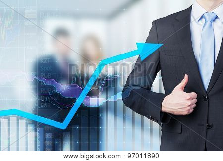 Businessman Thumb Up And Growing Arrow. Financial Charts And Business Couple In Blur On The Backgrou