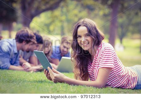 Pretty brunette using tablet in the park on a sunny day