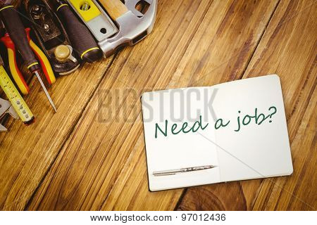 The word need a job? and notebook and pen against desk with tools