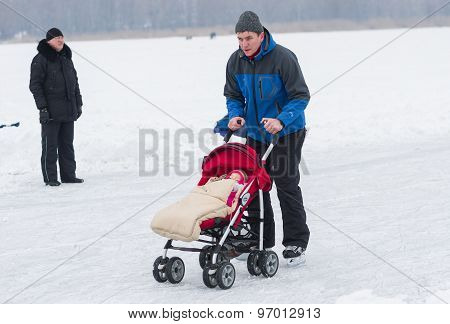 Active father skating with infant in baby carriage on a frozen river Dnepr