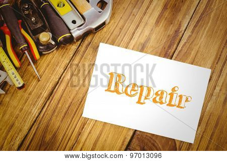 The word repair and white card against desk with tools