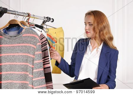 Seller In A Clothing Store Recalculates Goods On The Hanger