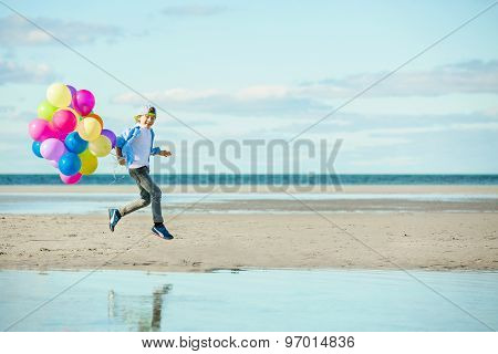 Happy boy plays with colored balloons on the beach