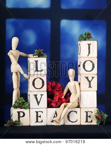 Love, Joy and Peace spelled out with rustic alphabet blocks in front of a night-time window.  Two mannequins, holly and a small bouquet of poinsettias adorn the blocks.
