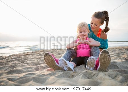 Fit Young Mother And Daughter Sitting On The Beach At Sunset