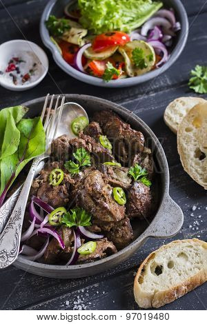 Fried Chicken Liver In A Pan And Grilled Vegetables On A Dark Wooden Background