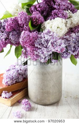 Beautiful Lilac In Watering Can On White Wooden Background