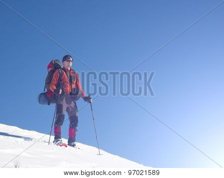 A Man In Snowshoes Is In The Mountains.