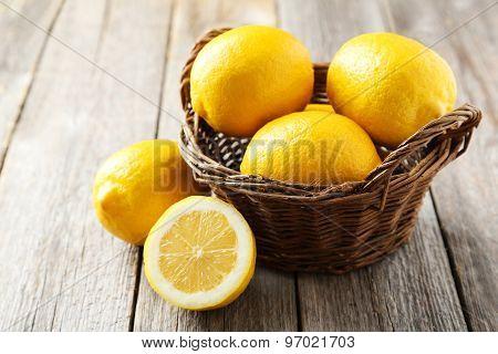 Lemons In Basket On Grey Wooden Background