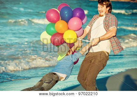 Happy father and son having great time on the beach in sunset light