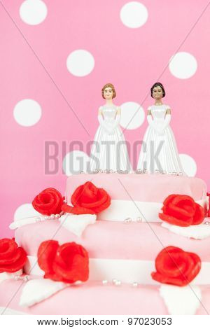 Pink wedding cake with red roses and lesbian couple on top