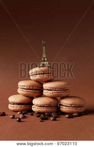 French Chocolate Macaroons With Coffee Beans On Brown Background