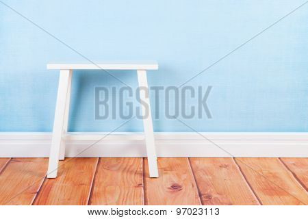 Little white table in interieur with blue wall paper