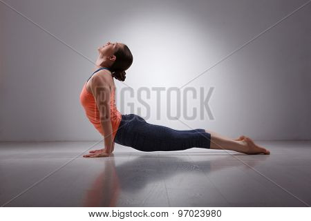 Beautiful sporty fit yogini woman practices yoga asana urdhva mukha svanasana - upward facing dog pose in studio