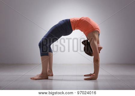 Beautiful sporty fit yogini woman practices yoga asana chakrasana (or urdva dhanurasana)  - wheel pose (or upward facing bow) pose in studio