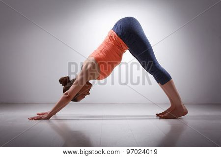 Beautiful sporty fit yogini woman practices yoga asana adhomukha svanasana - downward facing dog pose in studio