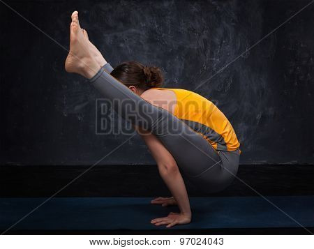 Beautiful sporty fit yogini woman practices yoga asana titibhasana - firefly pose on dark background