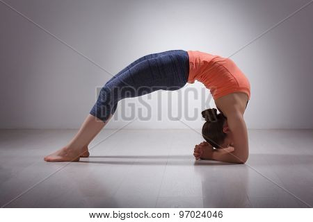 Beautiful sporty fit yogini woman practices yoga asana viparita dandasana - upward facing two feet staff pose in studio