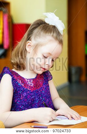 The Girl Sitting At The Table And Drawing With Colored Pencils