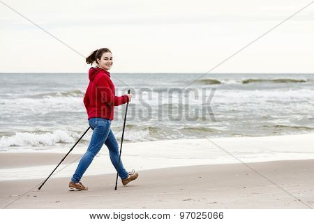 Nordic walking - young woman working out on beach