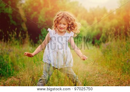 happy curly child girl running on the road on the walk in summer country side