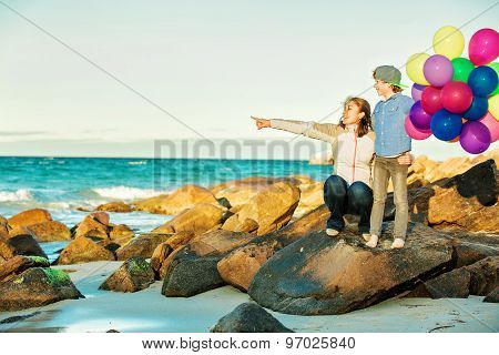 Happy mother and son having great time on the beach in sunset light