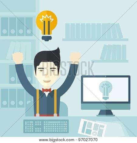 A young chinese guy is happy raising his two hands getting an idea through computer internet inside his office. Successful concept. A Contemporary style with pastel palette, soft blue tinted
