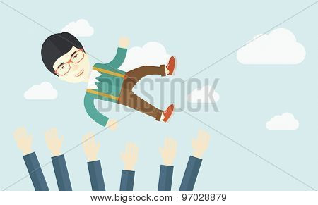 An aggressive japanese businessman being throwing up to the sky by his teamwork or colleague. Happiness concept. A contemporary style with pastel palette soft blue tinted background with desaturated