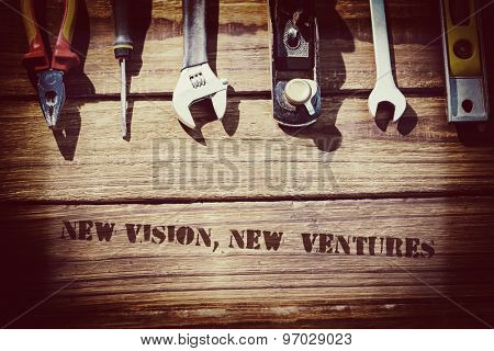 The word new vision, new ventures against desk with tools