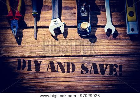The word diy and save! against desk with tools