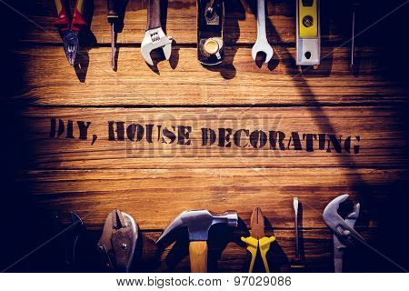 The word diy, house decorating against desk with tools