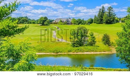 Golf place with pond and custom built luxury big house on background.