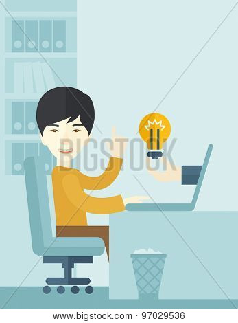 An asian businessman sitting while working in front of his desk getting a brilliant idea for business from the laptop. Business concept. A contemporary style with pastel palette soft blue tinted
