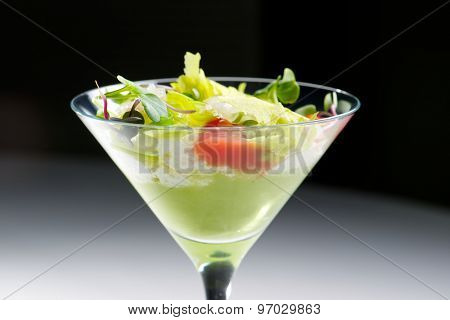 Tomato and green vegetables salad served in crystal glass.