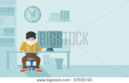 An overworked japanese businessman sitting infront of computer holding his head by two hands, under stress causing a headache. Unhappy concept. A contemporary style with pastel palette soft blue