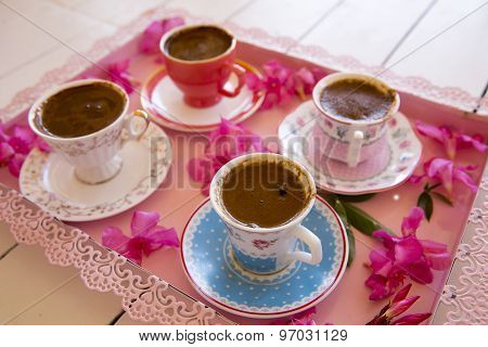 Four Small Cups Of Traditional Foamy Turkish Coffee Serving On A Colorful Flowery Pink Tray
