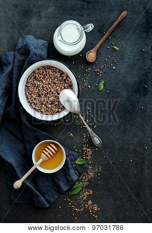 Rustic healthy breakfast set. Cooked buckwheat groats with milk and honey on dark grunge backdrop
